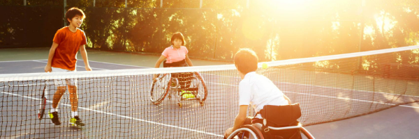 Participants playing wheelchair tennis